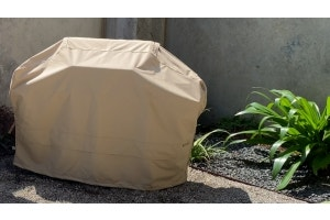 A clean grill cover in a backyard