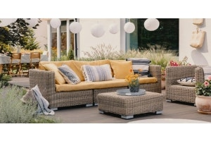 Patio furniture with pillows and cushions outside a house