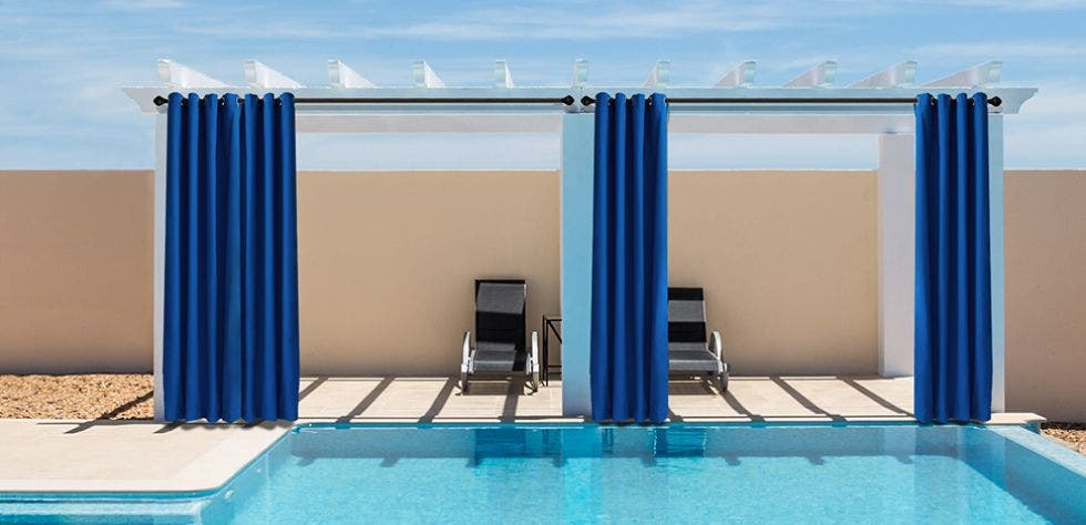 Blue outdoor curtains hanging next to a pool