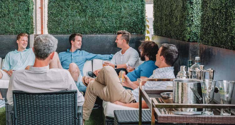 Group of friends sitting on patio furniture together