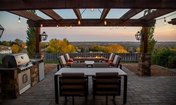 Backyard patio with an island grill, dining table, and fire pit
