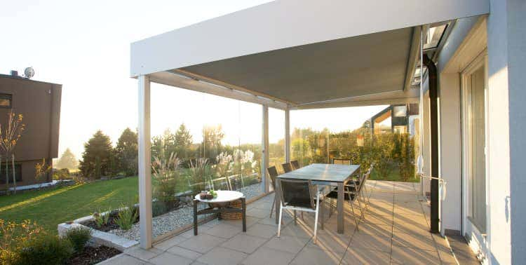 Dining table and chairs beneath a covered patio